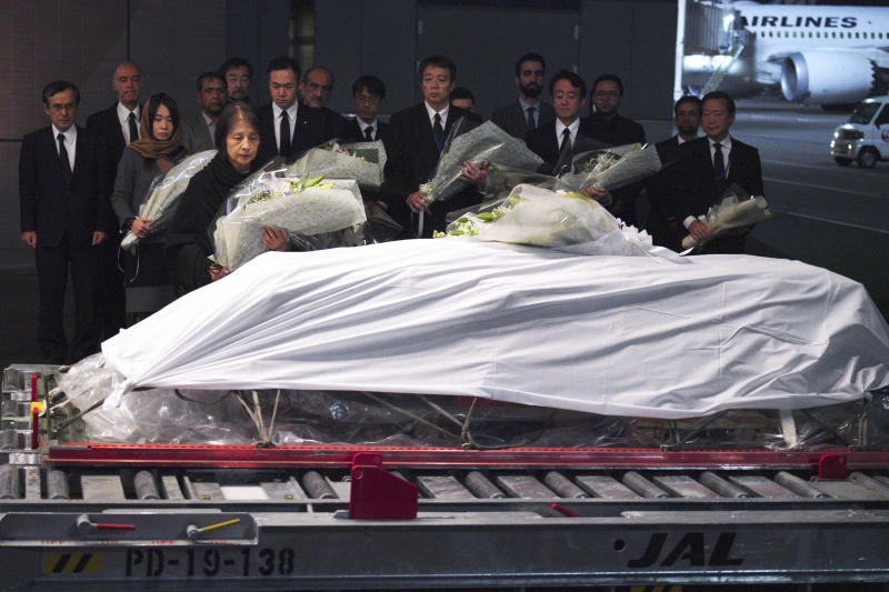 Family members and officials lay flowers at the coffin of slain Japanese doctor Tetsu Nakamura during a ceremony after transporting his body to his homeland, at Narita International Airport in Narita, east of Tokyo Sunday, Dec. 8, 2019. (AP Photo/Eugene Hoshiko)