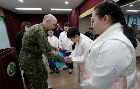 Canadian Lieutenant-General Wayne D. Eyre, Deputy Commander of United Nations Command, left, congratulates graduates during a graduation ceremony at Taesungdong freedom village inside the demilitarized zone between North and South Korea, near the border vi