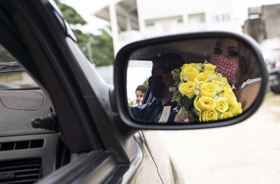 A bride is reflected on a car rearview window as she holds her bouquet after her drive-thru wedding at the neighborhood of Santa Cruz in Rio de Janeiro, Brazil, Thursday, May 28, 2020. Couples unable to have a traditional wedding because of the coronavirus pandemic are now taking part in drive-thru weddings. (AP Photo/Silvia Izquierdo)