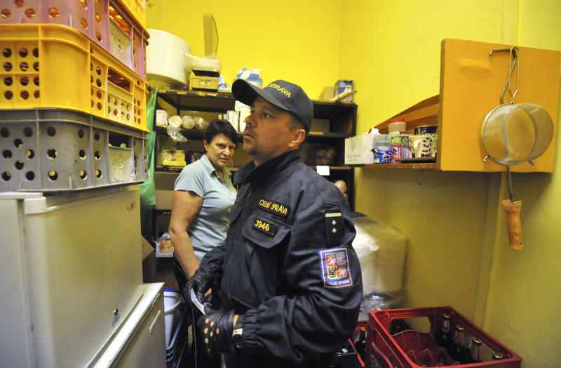 A shop assistant watches a policeman who searches   the inside of a stall in Ostrava, about 280 kilometres east of Prague, early Thursday, Sept. 13, 2012. The Czech government Wednesday approved a ban on sales of liquors containing more than 30 percent of alcohol in stalls and market places in the whole country, following a series of deaths from drinking bootleg alcohol. The ban was declared indefinitely. Methyl alcohol has claimed minimally 16 lives since September 6 when the first three people died. About 30 people have been hospitaliszed. Some of them are in a critical condition. Those who survive are threatened with life impairment of their health. (AP Photo/CTK, Jaroslav Ozana) SLOVAKIA OUT