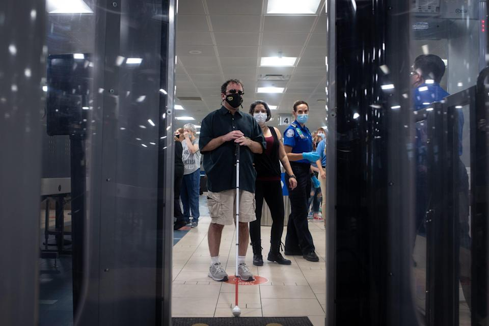 Jim Macklin (center, Foundation for Blind Children) waits to go into the body scanner during a TSA Cares tour on Sept. 14, 2021, in Terminal 4 at Phoenix Sky Harbor International Airport.