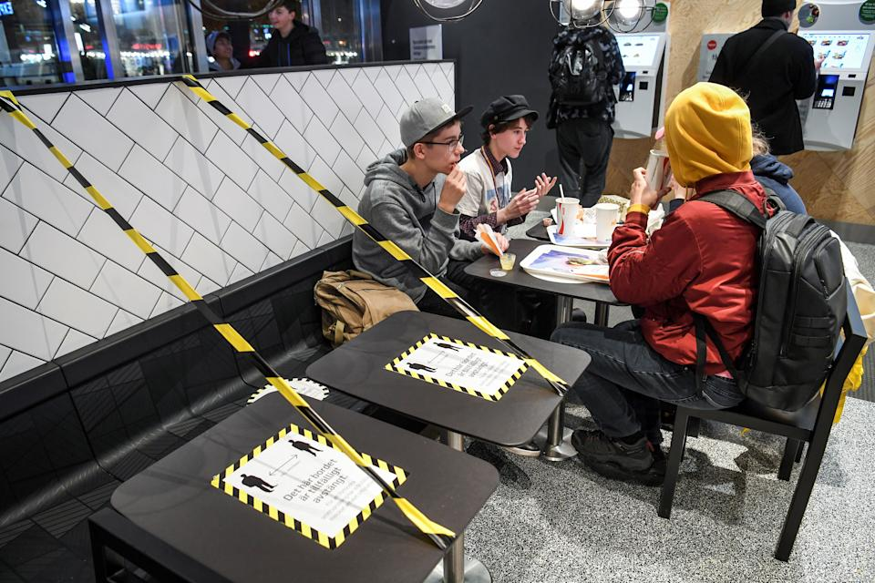 Guests enjoy their meal at a fast food restaurant next to taped off tables in central Stockholm on November 12, 2020, amid the ongoing novel coronavirus (Covid-19) pandemic. - The Swedish government has proposed a stop for the sale of alcohol after 10 pm from November 20 until the end of February, to curb the spread of the virus. Faced with the worsening of the Covid-19 epidemic in the country, the Swedish government on November 11 urged the population to follow health rules, although they are not coercive. (Photo by Fredrik SANDBERG / TT News Agency / AFP) / Sweden OUT (Photo by FREDRIK SANDBERG/TT News Agency/AFP via Getty Images)