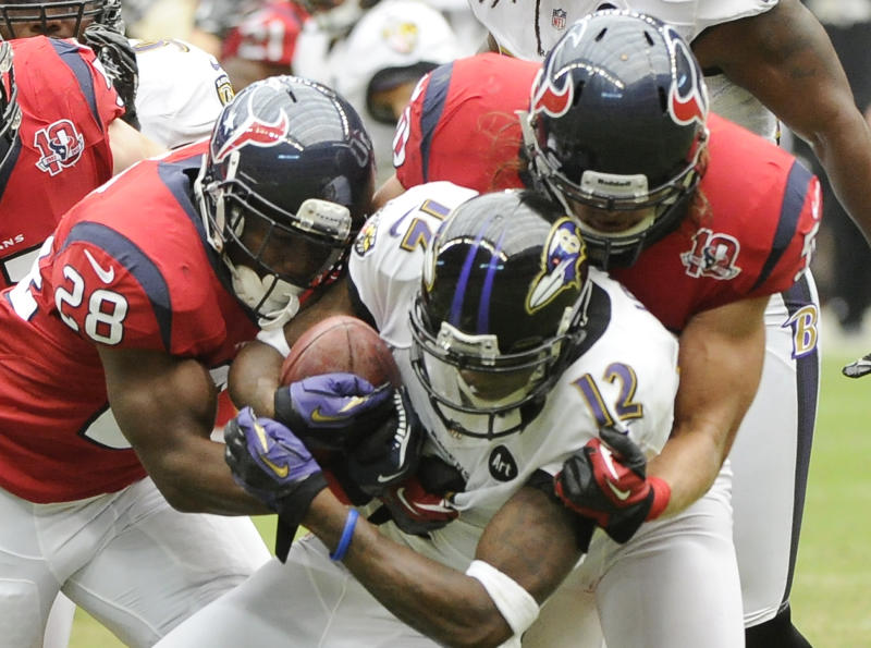 Houston Texans running back Justin Forsett (28) and Bryan Braman (50) tackle Baltimore Ravens wide receiver Jacoby Jones (12) during the second quarter of an NFL football game Sunday, Oct. 21, 2012, in Houston. (AP Photo/Dave Einsel)