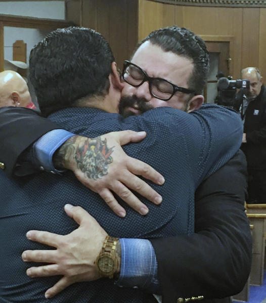 """Christopher """"Jake"""" Carrizal, right, gets a hug following a mistrial, Friday, Nov. 10, 2017, in Waco, Texas. The Dallas chapter president of the Bandidos motorcycle club is the first to stand trial involving the 2015 shootout where nine people were fatally shot and 18 people were injured outside of Twin Peaks restaurant. (Tommy Witherspoon/Waco Tribune-Herald via AP)"""