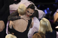 Charlize Theron, left, embraces Gal Gadot in the audience at the Oscars on Sunday, Feb. 9, 2020, at the Dolby Theatre in Los Angeles. (AP Photo/Chris Pizzello)