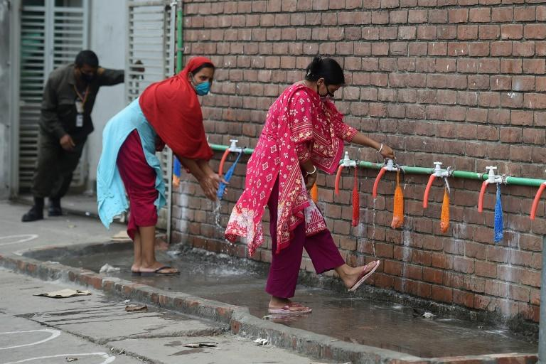 Garment workers wash their legs before entering a factory in Dhaka, Bangladesh, where hundreds of such factories reopened despite a nationwide lockdown against new coronavirus (AFP Photo/MUNIR UZ ZAMAN)