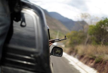 A vigilante aims his weapon out of a car window while driving in a convoy with others to Poturo December 29, 2013. REUTERS/Jorge Dan Lopez/Files