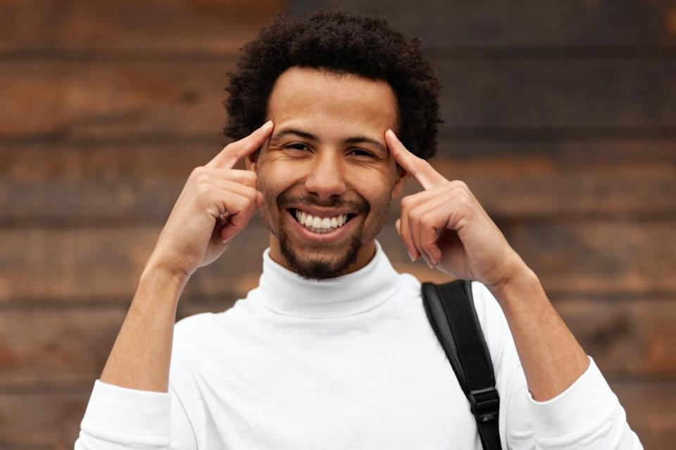 Smiling African man holds his hands at his head.