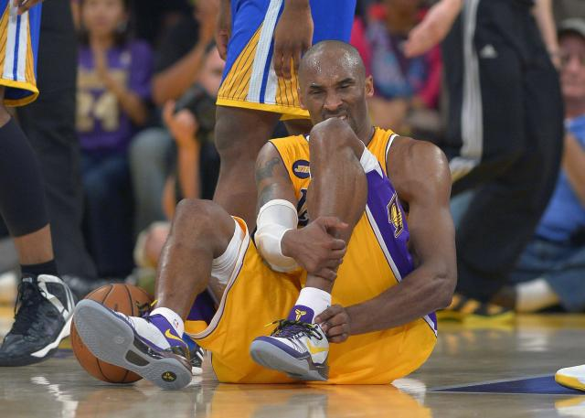 FILE - In this April 12, 2013 file photo, Los Angeles Lakers guard Kobe Bryant grimaces after being injured during the second half of their NBA basketball game against the Golden State Warriors, in Los Angeles. Bryant won't be back on the court for the Lakers this season. The Lakers said Bryant was examined by team physician Dr. Steve Lombardo, who determined that the left knee injury that has kept Bryant out of the lineup still hasn't healed. (AP Photo/Mark J. Terrill, File)