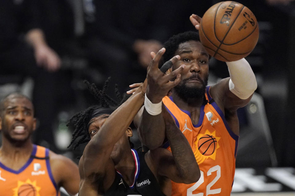 Los Angeles Clippers guard Terance Mann, left, and Phoenix Suns center Deandre Ayton reach for a rebound during the second half in Game 6 of the NBA basketball Western Conference Finals Wednesday, June 30, 2021, in Los Angeles. (AP Photo/Mark J. Terrill)