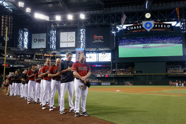 <p>Arizona Diamondbacks manager Chip Hale, right, hitting coach Dave Magadan, second from right, pitching coach Mike Butcher, third from right, and bench coach Glenn Sherlock, fourth from right, join other Diamondbacks coaches and players for a moment of silence for the Orlando, Fla., mass shooting victims prior to a baseball game against the Miami Marlins, June 12, 2016, in Phoenix. (AP Photo/Ross D. Franklin) </p>