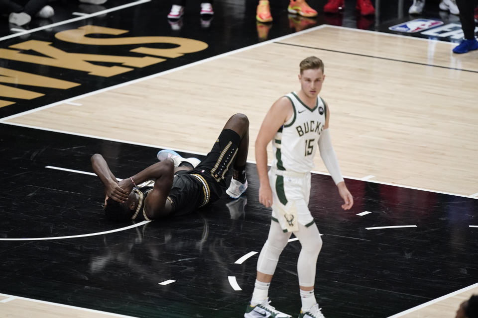 Atlanta Hawks' Clint Capela (15) lies on the court after being hit during the second half against the Milwaukee Bucks in Game 4 of the NBA basketball Eastern Conference finals Tuesday, June 29, 2021, in Atlanta. (AP Photo/Brynn Anderson)