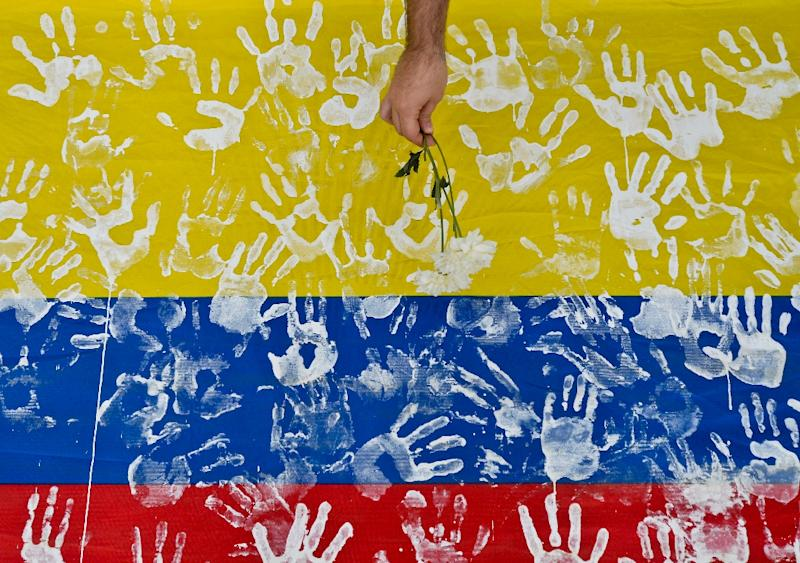 A man places a flower on a Colombian national flag during a march along the streets of Cali, Colombia, in support of peace talks, on July 15, 2016
