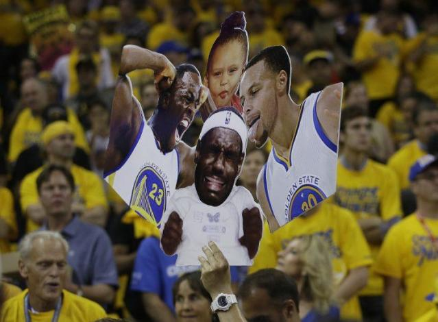 A Warriors fan holds up photos of Draymond Green, Stephen Curry, and Curry's daughter, Riley, to mockLeBron James. (AP)