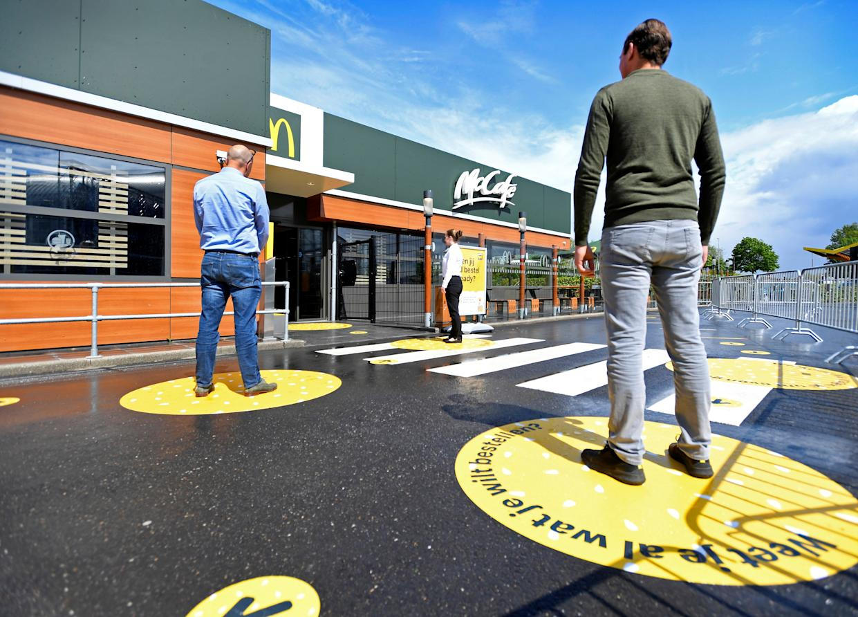 Customers wait outside on social distancing markings at a prototype location of fast food giant McDonald's for restaurants which respect the 1.5m social distancing measure, amid the coronavirus disease (COVID-19) outbreak, in Arnhem, Netherlands, May 1, 2020. REUTERS/Piroschka van de Wouw