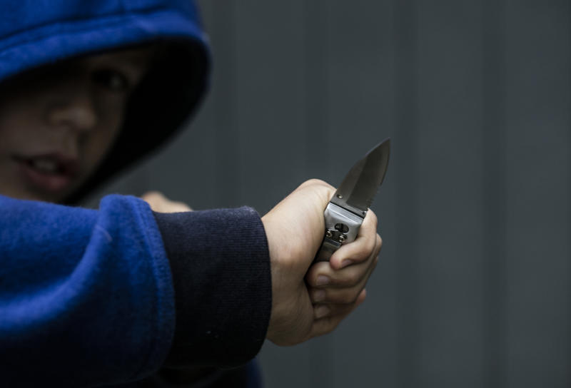 Boy holding knife ready to attack someone