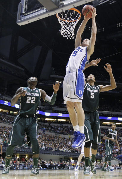 Duke forward Mason Plumlee (5) goes up with a shot against Michigan State forwards Branden Dawson (22) and Adreian Payne (5) during the second half of a regional semifinal in the NCAA college basketball tournament, Friday, March 29, 2013, in Indianapolis. (AP Photo/Michael Conroy)