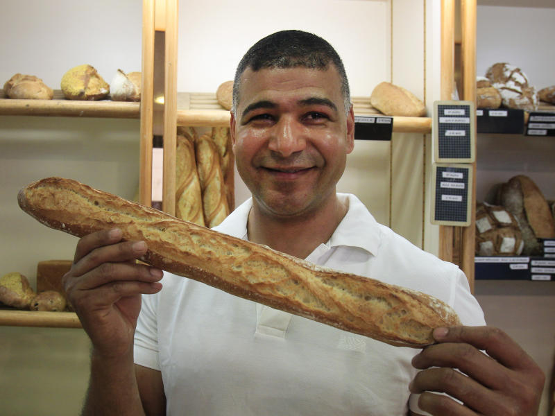 Ridha Khadher a Tunisian born baker stands in his Paris bakery, as he poses with one of his baguette, after winning the title of Best Baguette of Paris, Friday April 26, 2013.  This award makes him the baguette supplier for the Elysee Palace, home of the French Presidency. (AP Photo/Remy de la Mauviniere)