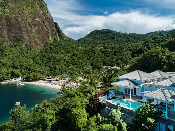 """The Work From Hotel package at <a href=""""https://www.viceroyhotelsandresorts.com/sugar-beach"""" rel=""""nofollow noopener"""" target=""""_blank"""" data-ylk=""""slk:Sugar Beach, a Viceroy Resort,"""" class=""""link rapid-noclick-resp"""">Sugar Beach, a Viceroy Resort,</a> in St. Lucia starts at $31,470 for a 30-night stay on the 100-acre property and is the epitome of opulence. Think private airport transfers, a personal terrace and plunge pool, a poolside cabana stocked with fresh fruit and water and, if none of that has sold you, your very own butler. All visitors to the island must arrive with a negative COVID-19 test, taken no more than seven days before arrival."""