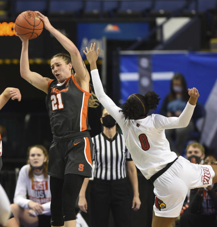 Syracuse's Emily Engstler pulls down a defensive rebound under pressure from Louisville's Ramani Parker during an NCAA college basketball game in the semifinals of Atlantic Coast Conference tournament in Greensboro, N.C., Saturday, March 6, 2021. (Walt Unks/The Winston-Salem Journal via AP)