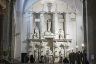 Visitors admire the tomb of Pope Julius II, with the central marble statue of Mosè, made by Italian sculptor Michelangelo Buonarroti between 1505 and 1545, inside the San Pietro in Vincoli church, in Rome, Friday, Dec. 11, 2020. Like elsewhere in Europe, museums and art galleries in Italy were closed this fall to contain the spread of COVID-19, meaning art lovers must rely on virtual tours to catch a glimpse of the treasures held by famous institutions such as the Uffizi in Florence and the Vatican Museums in Rome. However, some exquisite gems of Italy's cultural heritage remain on display in real life inside the country's churches, some of which have collections of renaissance art and iconography that would be the envy of any museum. (AP Photo/Andrew Medichini)