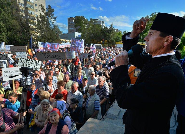 Vasile Laiu, the Orthodox archpriest of Barlad, prays during a protest against shale gas exploition in Barlad city on May 27, 2013. For months the 50-year-old cleric has been one of the most outspoken opponents to plans by US energy giant Chevron to drill for shale gas in this rural and impoverished region