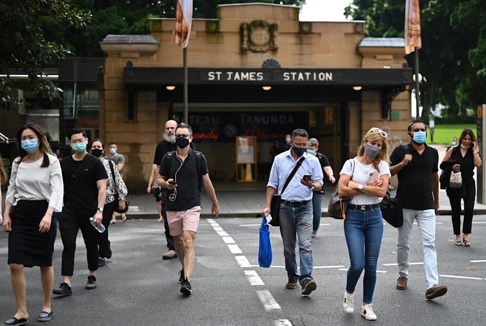 Commuters wearing face masks exit St. James Station in the CBD in Sydney. Source: AAP