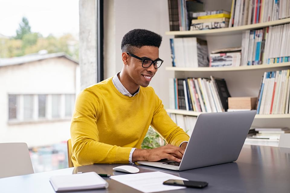 Successful african american businessman using computer at modern office. Happy creative young man feeling successful after receiving approval mail from client and working from home. Smiling student working and studying on computer sitting at desk.