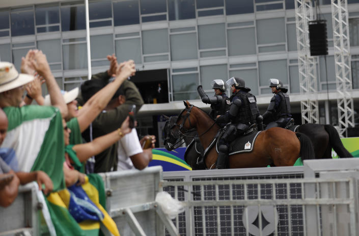 People greet military police officers before the swearing-in ceremony of former army captain Jair Bolsonaro as Brazil's new President in front of the Planalto palace in Brasilia, Brail, Tuesday Jan. 1, 2019. Once an outsider mocked by fellow lawmakers for his far-right positions, constant use of expletives and even casual dressing, Bolsonaro is taking office as Brazil's president Tuesday. (AP Photo/Silvia Izquierdo)