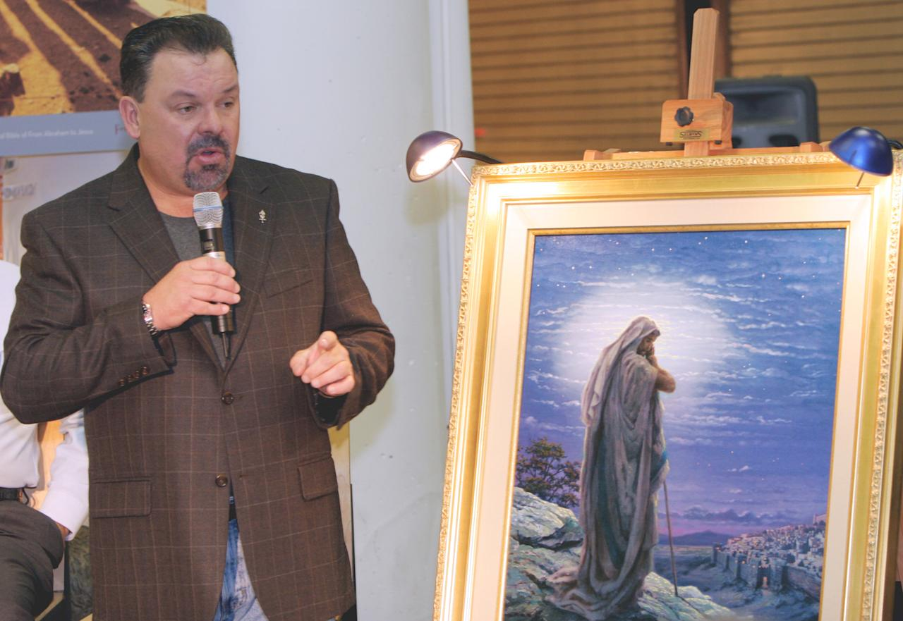 "FILE - In this Sept. 15, 2006 file photo, artist Thomas Kinkade unveils his painting, ""Prayer For Peace,"" at the opening of the exhibit ""From Abraham to Jesus,"" in Atlanta. Kinkade, whose brushwork paintings of idyllic landscapes, cottages and churches have been big sellers for dealers across the United States, died Friday, April 6, 2012, a family spokesman said. He was 54. (AP Photo/Gene Blythe, File)"