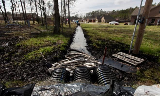 Spilled oil is seen in a drainage ditch near evacuated homes in Mayflower, Ark., on March 31, 2013.