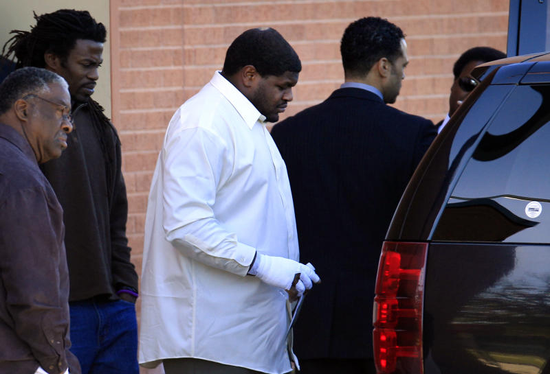 """FILe - In this Dec. 11, 2012 file photo, Dallas Cowboys defensive tackle Josh Brent, center, with a bandaged hand, leaves with unknown persons after a memorial service for practice squad member Jerry Brown at Oak Cliff Bible Fellowship in Dallas. Brent retired from football Thursday, July 18, 2013, saying """"doing the right things in life"""" is more important as he prepares to defend himself against a manslaughter charge in a drunken-driving crash that killed Brown. (AP Photo/LM Otero, File)"""