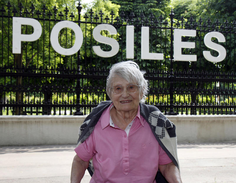 Edeltrud Posiles poses in front of her name that was attached on a fence in downtown Vienna, on Friday, May 13, 2011. 94-year old Posiles is the last one of 88 Austrians known to have saved Jews from the Holocaust who is still alive. She has hidden her Jewish fiance and his two brothers. They had fled to Prague after the Nazi annexation of Austria in 1938. But by 1942, that city too was in the hands of Hitler's henchmen. The three were told to pack essentials for deportation into a concentration camp. They wrote suicide letters to make authorities think they were dead _ and then did what no one thought any Jew would do, taking a night train straight to Vienna, back into the heartland of the Nazi Reich. (AP Photo/Ronald Zak)