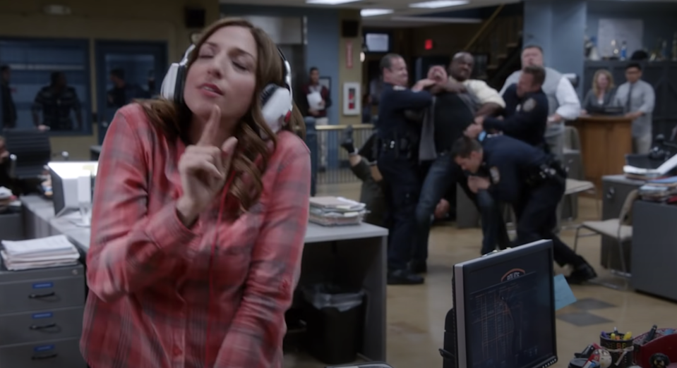 Gina dancing with headphones, oblivious so the fight behind her