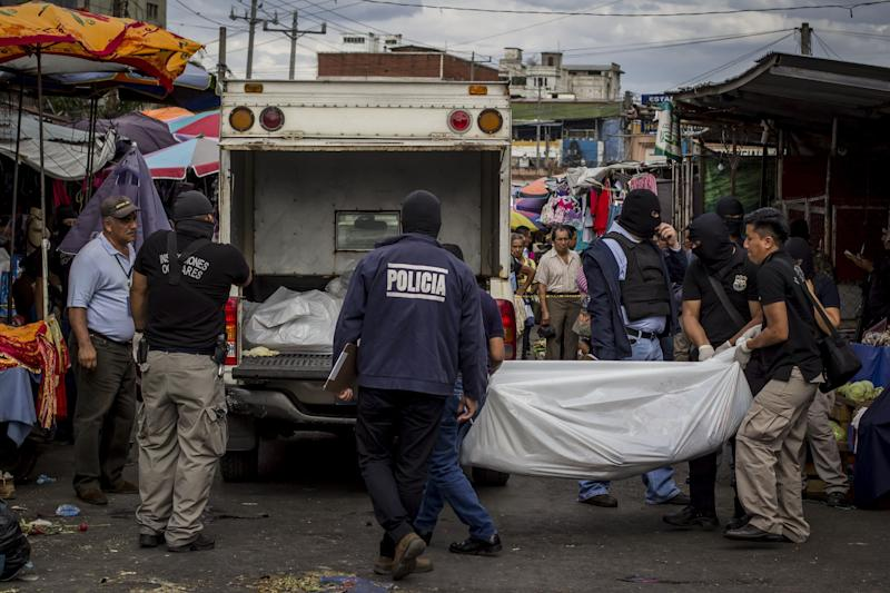 Police investigators carry a body to a forensic vehicle, after a shootout between private security guards and gang members, at the central market in San Salvador, El Salvador, Wednesday, March 15, 2017. At least 30 people, mostly gang members, died in the last 24 hours in El Salvador on one of the most violent days so far this year. (AP Photo/Salvador Melendez)