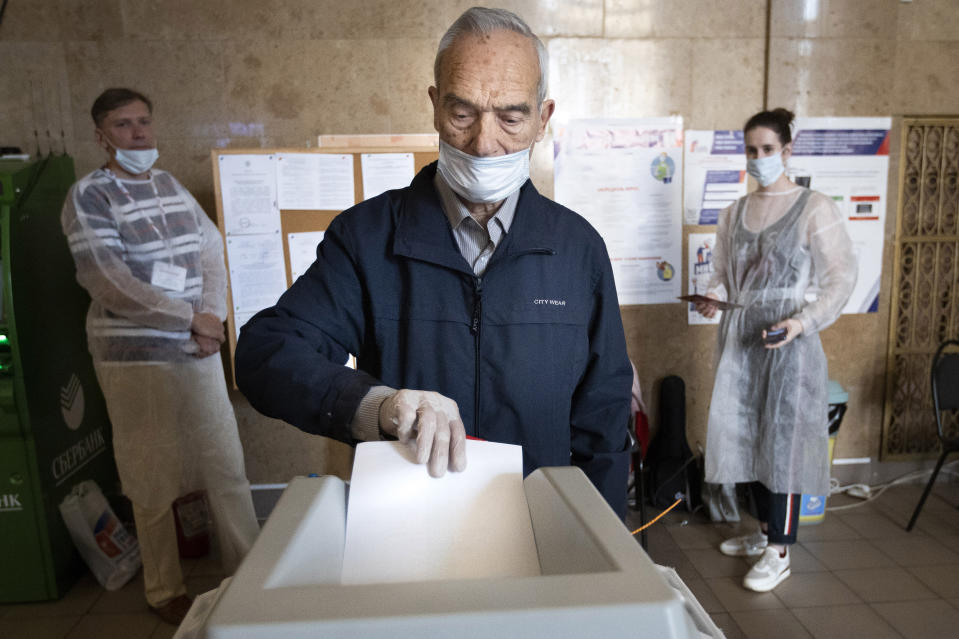 A man wearing a face mask and gloves to protect against coronavirus casts his ballot at a polling station in Moscow, Russia, Wednesday, July 1, 2020. The vote on the constitutional amendments that would reset the clock on Russian President Vladimir Putin's tenure and enable him to serve two more six-year terms is set to wrap up Wednesday. (AP Photo/Alexander Zemlianichenko)