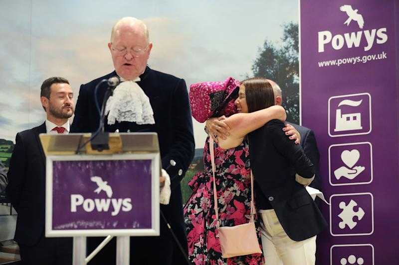 Liberal Democrat candidate Jane Dodds (R) is congratulated by the Official Monster Raving Loony Party candidate Lady Lily The Pink after winning the Brecon and Radnorshire by-election at the Royal Welsh Showground on August 2, 2019 in Builth Wells, Wales. - Britain's Boris Johnson lost his first major test as prime minister on August 2 when his candidate lost to a pro-EU rival in a by-election that could narrow his parliamentary majority to one. Official results showed the European-supporting Liberal Democrats' candidate Jane Dodds defeating Chris Davies from Johnson's ruling Conservative party by 13,826 to 12,401 votes. (Photo by Isabel INFANTES / AFP) / The erroneous mention appearing in the metadata of this photo by Isabel INFANTES has been modified in AFP systems in the following manner: [Jane Dodds] instead of [Jane Dodd]. Please immediately remove the erroneous mention from all your online services and delete it from your servers. If you have been authorized by AFP to distribute it to third parties, please ensure that the same actions are carried out by them. Failure to promptly comply with these instructions will entail liability on your part for any continued or post notification usage. Therefore we thank you very much for all your attention and prompt action. We are sorry for the inconvenience this notification may cause and remain at your disposal for any further information you may require. (Photo credit should read ISABEL INFANTES/AFP/Getty Images)