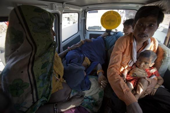 Anguri (in blue sari), a 26-year-old pregnant woman in labour, lies on a bench inside a maternity ambulance as her relatives accompany her to a community health centre in a rural area near the remote village of Chharchh, in the central Indian state of Madhya Pradesh, February 24, 2012.