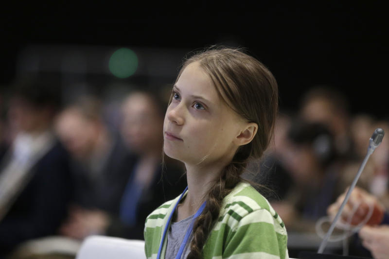 FILE - In this Wednesday, Dec. 11, 2019, file photo, Swedish climate activist Greta Thunberg listens to speeches before addressing the U.N. climate conference n Madrid, Spain. On Friday, Dec. 13, 2019, The Associated Press reported on a video circulating online and inaccurately described, in some social media posts, as showing Thunberg firing an AR-15 rifle. The shooter in the video is another young Swede named Emmy Slinge. (AP Photo/Paul White)