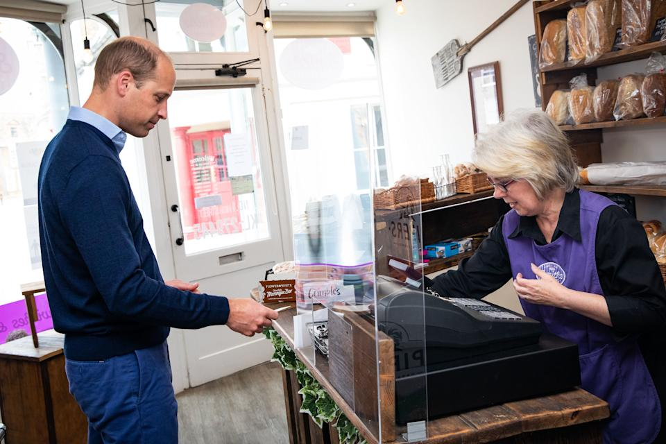 Britain's Prince William, Duke of Cambridge, uses contactless payment to pay owner Teresa Brandon for his purchases during a visit to Smiths the Bakers in the High Street in King's Lynn, eastern England on on June 19, 2020. - The Duke visited the independent business to hear about the impact of the Covid-19 pandemic. (Photo by Aaron Chown / POOL / AFP) (Photo by AARON CHOWN/POOL/AFP via Getty Images)