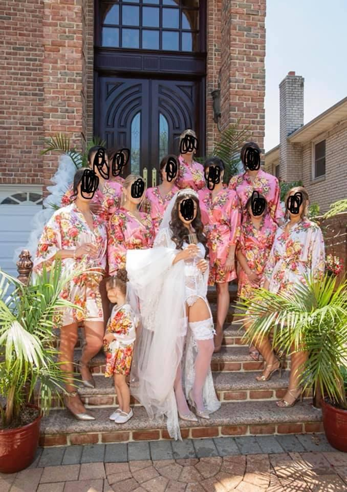 A photo of a bride dressed in white lingerie posing with her bridesmaids wearing pink floral robes.