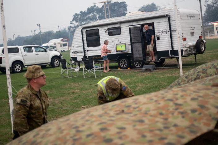 Members of a military support team deploy a tent as evacuees are seen at their caravan in the town of Eden