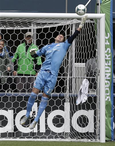 New England Revolution goalkeeper Bobby Shuttleworth stretches to reach the ball in the first half of an MLS soccer match against the Seattle Sounders, Saturday, April 13, 2013, in Seattle. (AP Photo/Ted S. Warren)