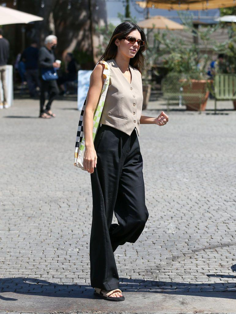 """<p>While out in Los Angeles Kendall Jenner gave us all a masterclass in summer suiting. </p><p>The model and business owner paired an oat-hued waistcoat with black, high-waisted, wide-legged suit trousers to create a minimal workwear look. To give it a season-appropriate twist, the tequila brand owner added camel and black sandals, tortoiseshell 1990s-style sunnies and a bright <a href=""""https://int.stinegoya.com/products/idunn-bag-accessories-checks?switch=FR"""" rel=""""nofollow noopener"""" target=""""_blank"""" data-ylk=""""slk:checkerboard print bag by Stine Goya"""" class=""""link rapid-noclick-resp"""">checkerboard print bag by Stine Goya</a>.</p><p><a class=""""link rapid-noclick-resp"""" href=""""https://go.redirectingat.com?id=127X1599956&url=https%3A%2F%2Fwww.mytheresa.com%2Fen-gb%2Ffrankie-shop-button-down-vest-1676098.html&sref=https%3A%2F%2Fwww.elle.com%2Fuk%2Ffashion%2Fcelebrity-style%2Farticles%2Fg2543%2Fkendall-jenner%2F"""" rel=""""nofollow noopener"""" target=""""_blank"""" data-ylk=""""slk:SHOP WAISTCOAT NOW"""">SHOP WAISTCOAT NOW</a></p>"""