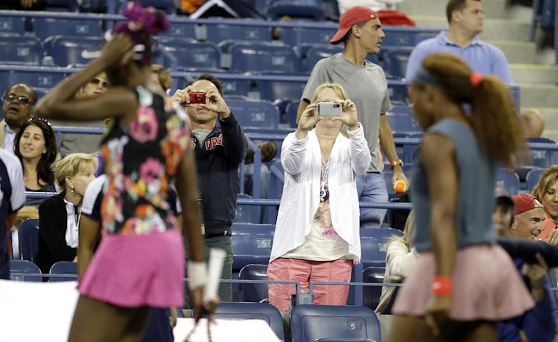 Tennis fans take photos as Venus Williams, left, and Serena Williams walk to their bench for a break between games against Lucie Hradecka, of the Czech Republic, and Andrea Hlavackova, of the Czech Republic, during the women's doubles semifinals of the 2013 U.S. Open tennis tournament, Friday, Sept. 6, 2013, in New York. (AP Photo/Darron Cummings)