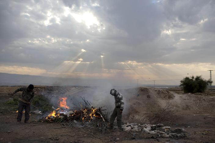 Palestinian farmers burn agriculture waste just outside the West Bank Jordan Valley Jewish settlement of Petsael, Thursday, Jan. 9, 2014. For Israeli farmers in the West Bank's Jordan Valley, an international campaign to boycott settlement products has turned almost overnight from a distant nuisance into a harsh economic reality. The export-driven income of growers in the valley's 21 settlements dropped by 15 percent, or $29 million dollars, last year because Western European supermarket chains trying to avoid political entanglements largely stopped buying the valley's grapes, dates and sweet peppers. (AP Photo/Oded Balilty)