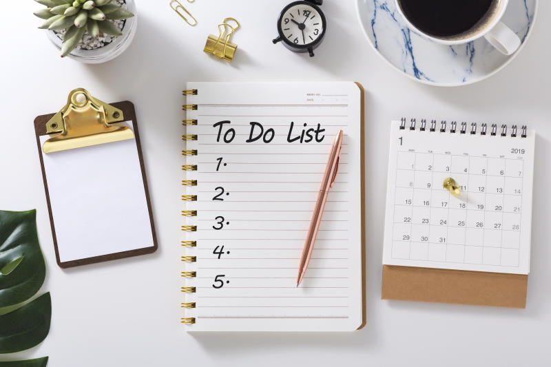 To do list in notebook with calendar and clock on white desk