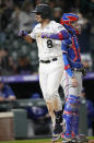 Colorado Rockies'' Joshua Fuentes celebrates as he crosses home plate after hitting a solo home run, next to Texas Rangers catcher Jonah Heim during the eighth inning of a baseball game Wednesday, June 2, 2021, in Denver. (AP Photo/David Zalubowski)