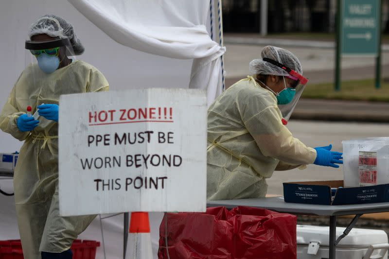 Healthcare workers prepare specimen collection tubes at a coronavirus disease (COVID-19) drive-thru testing location in Houston