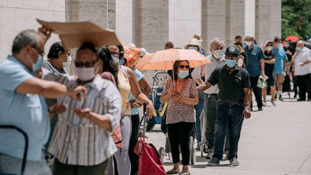 PHOTO: New Yorkers in need wait in a long line to receive free produce, dry goods, and meat at a Food Bank For New York City distribution event at Lincoln Center on July 29, 2020, in New York. (Scott Heins/Getty Images)